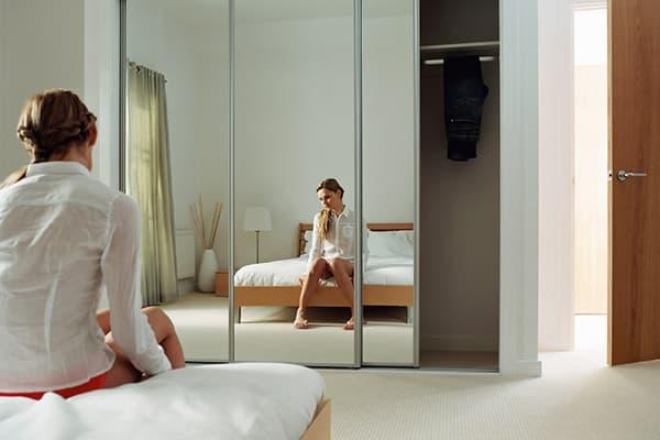 Девушка в плохом настроении перед зеркалом