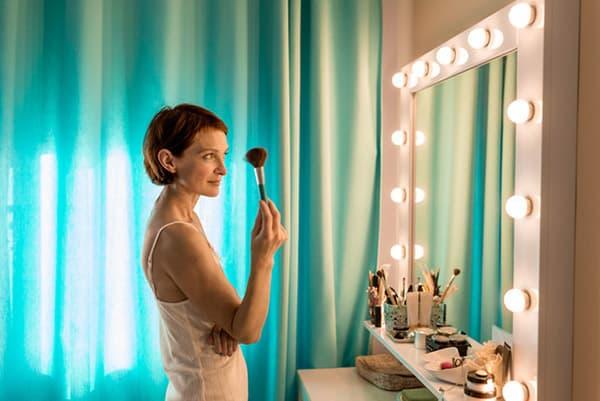 Женщина наносит макияж перед зеркалом