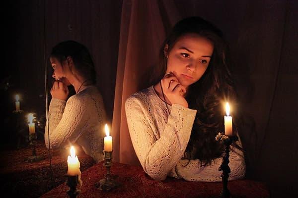 Девушка сидит у зеркала со свечами