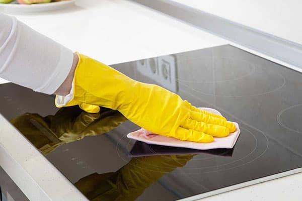 Хозяйка вытирает варочную поверхность салфеткой