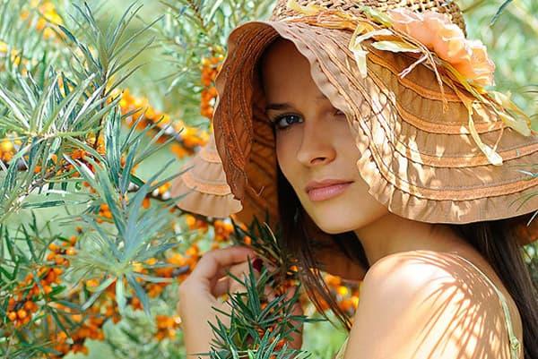 Девушка в шляпе возле куста облепихи