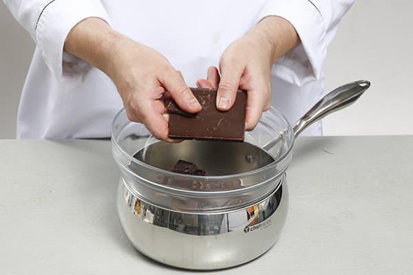 Кондитер топит шоколад на водяной бане