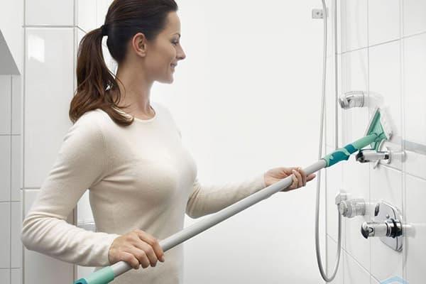 Девушка протирает кафель на стене  в ванной