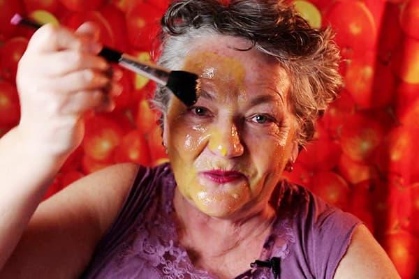 Пожилая женщина наносит яичную маску на лицо