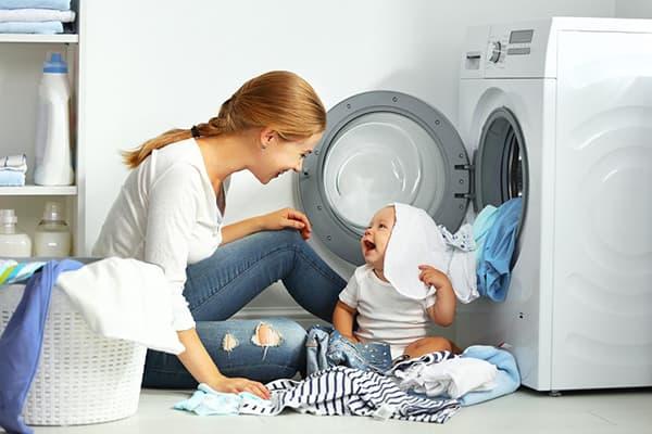 Мама с малышом разбирают вещи после стирки