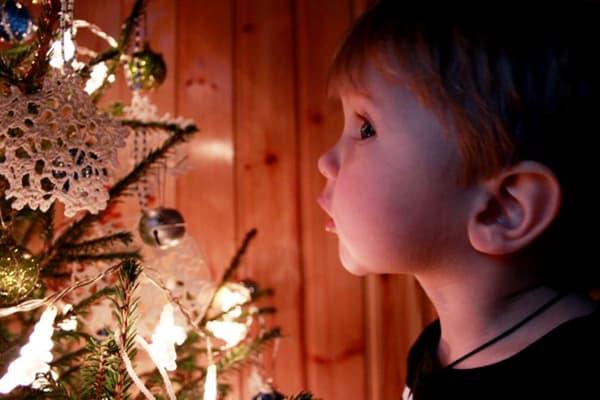 Ребенок около новогодней елки