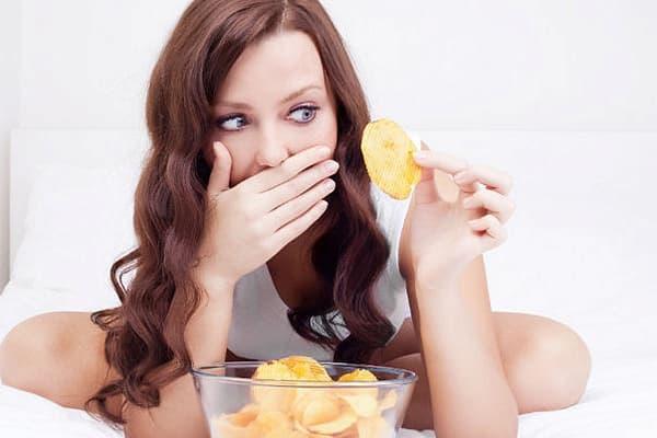 Девушка ест чипсы