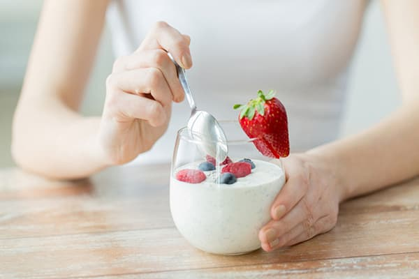 Девушка ест обезжиренный йогурт с ягодами