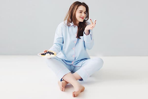 Девушка в пижаме ест пирог