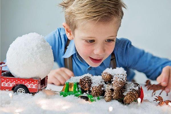 Мальчик играет с искусственным снегом
