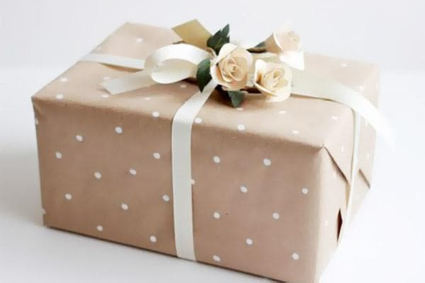 Подарок в крафтовой бумаге, декорированный лентами и розочками