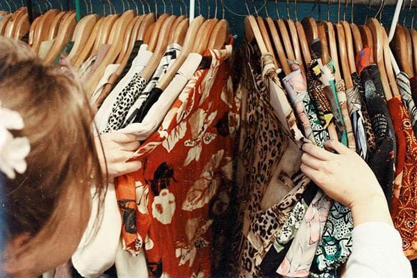 Женщина разбирает одежду в шкафу