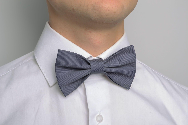 Мужчина в белой рубашке с серой бабочкой