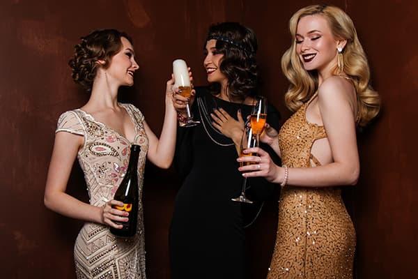 Девушки в вечерних платьях пьют шампанское