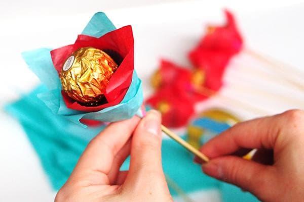 Женщина делает цветок из конфеты, шпажки и бумаги