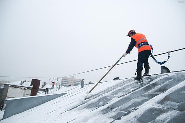 Работник ЖКХ чистит фальцевую кровлю от снега