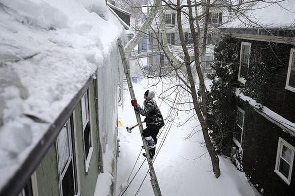 Мужчина лезет на заснеженную крышу по лестнице