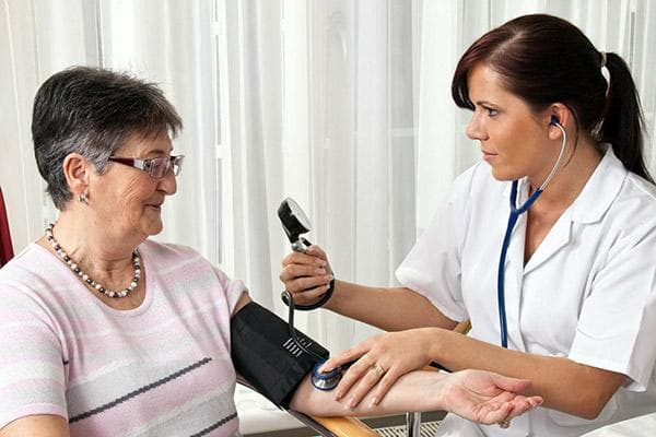 Врач измеряет давление пожилой пациентке