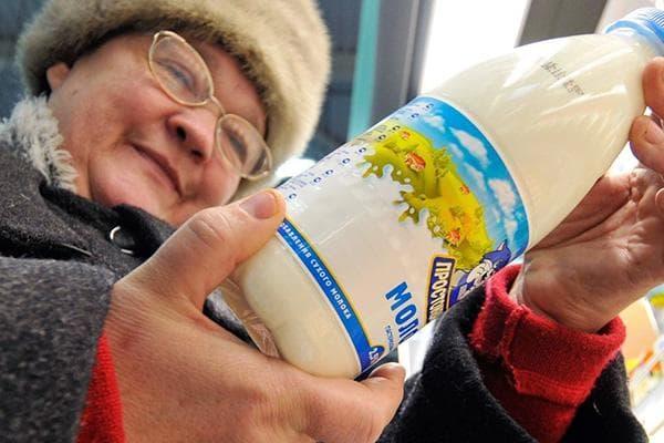 Пенсионерка выбирает молоко в магазине