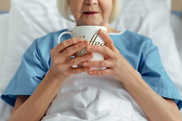 Пожилая женщина в постели пьет кофе