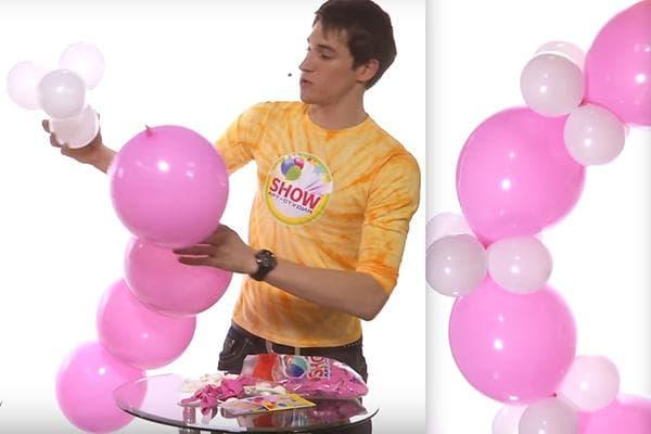 Мужчина делает арку из воздушных шариков