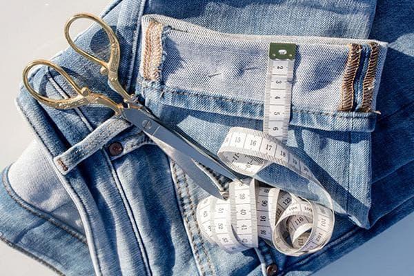 Старые джинсы, ножницы и сантиметровая лента