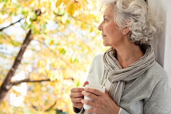 Пожилая женщина с чашкой в руках