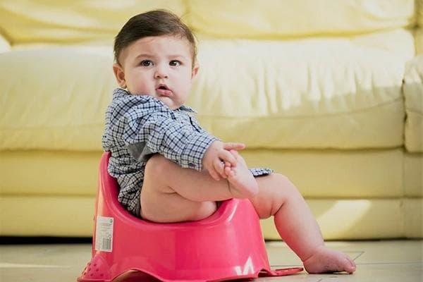 Ребенок на горшке возле дивана
