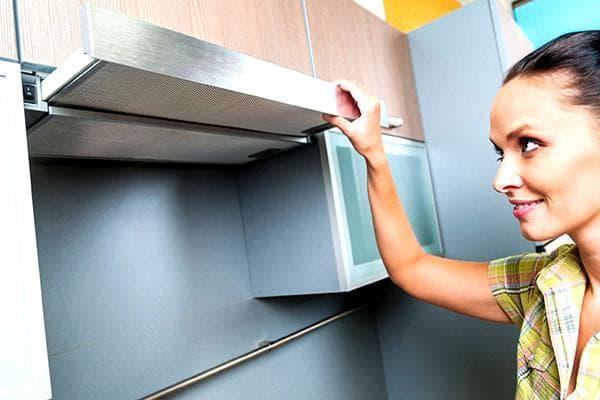 Женщина пользуется кухонной вытяжкой