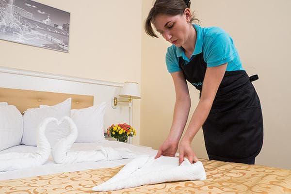 Женщина скручивает полотенце треугольником