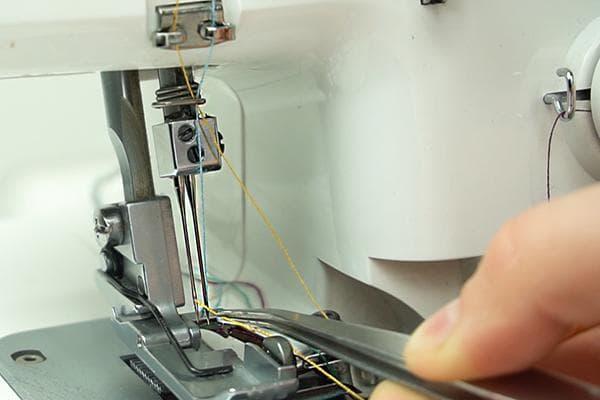 Заправка нитки в иглу оверлока пинцетом