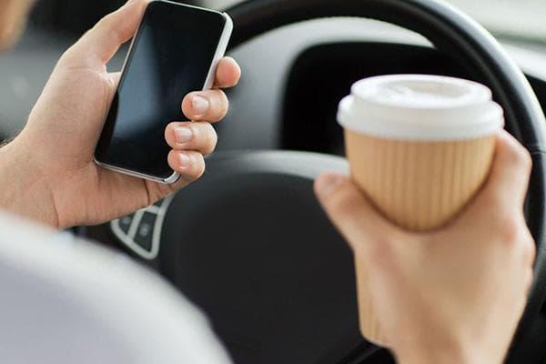 Водитель автомобиля пьет кофе