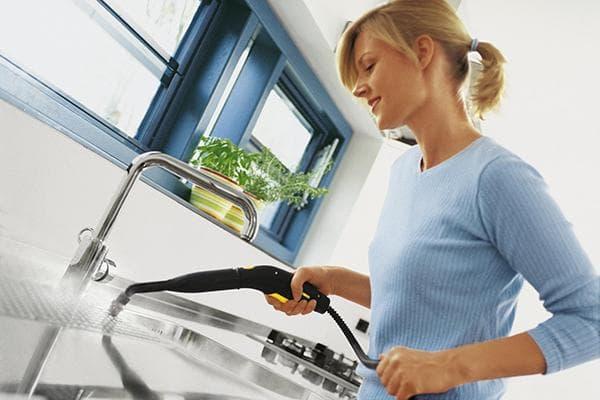 Женщина обрабатывает кухонные поверхности парогенератором
