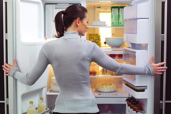 Женщина перед открытым холодильником