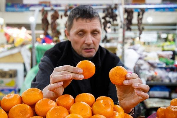 Мужчина выбирает мандарины