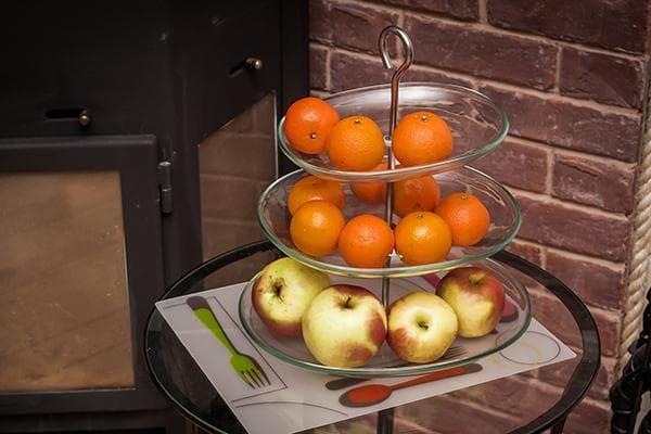 Мандарины и яблоки в этажерке для фруктов