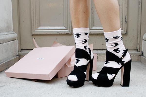 Девушка растягивает замшевые босоножки, надев их на носки