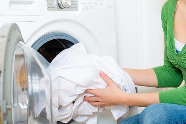 Загрузка постельного белья в стиральную машину