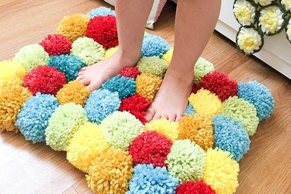 Коврик из разноцветных помпонов