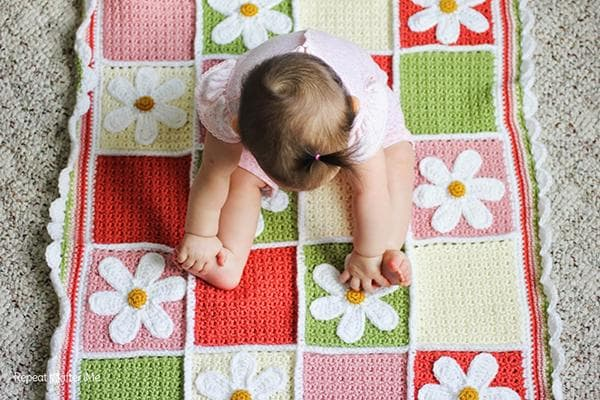 Маленькая девочка сидит на вязаном коврике
