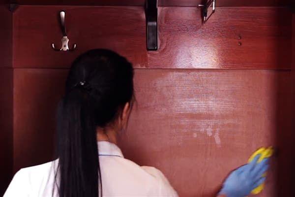 Женщина протирает уксусом заднюю стенку шкафа