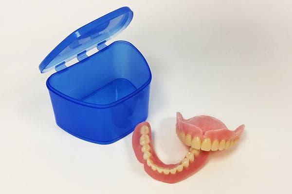 Зубные протезы и контейнер для их хранения