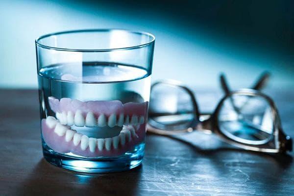 Зубной протез в стакане с водой