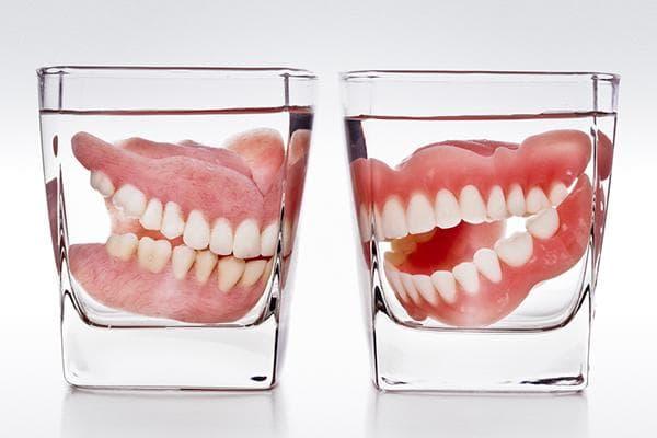 Зубные протезы в стаканах с водой