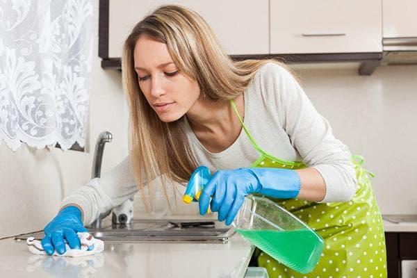 Женщина моет кухонную столешницу