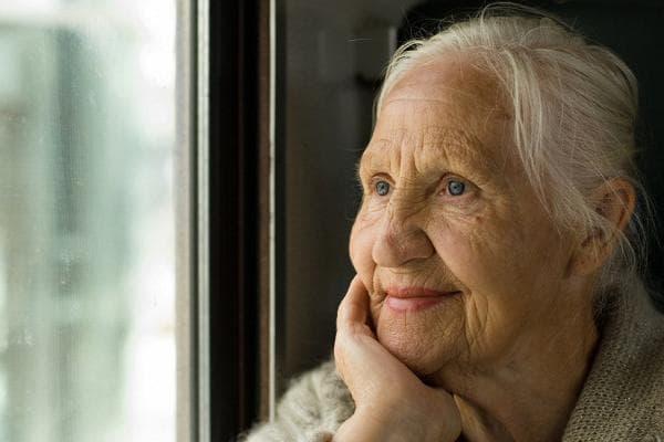 Пожилая женщина что-то вспоминает у окна