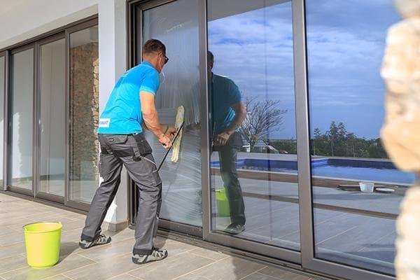 Мужчина моет панорамное окно