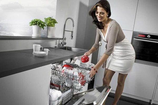 Женщина достает посуду из посудомоечной машины