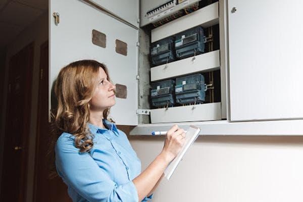 Женщина снимает показания счетчика электроэнергии