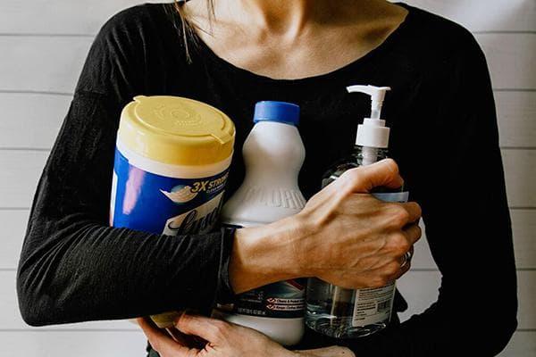 Женщина с дезинфицирующими средствами в руках